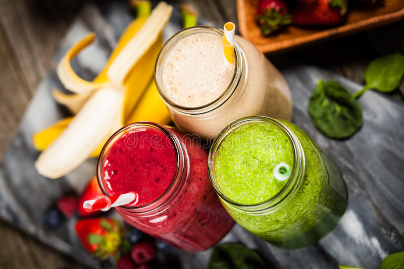 Milkshakes and smoothies. Assortment of milkshakes and smoothies on wooden table royalty free stock image