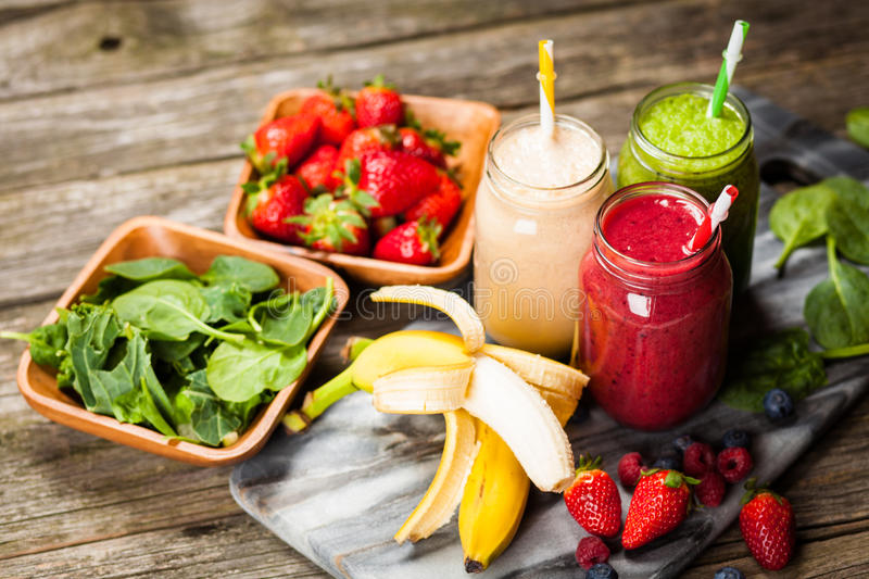Milkshakes and smoothies. Assortment of milkshakes and smoothies on wooden table royalty free stock images