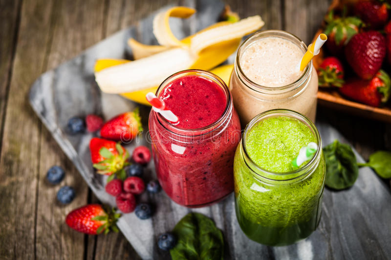 Milkshakes and smoothies. Assortment of milkshakes and smoothies on wooden table stock photos