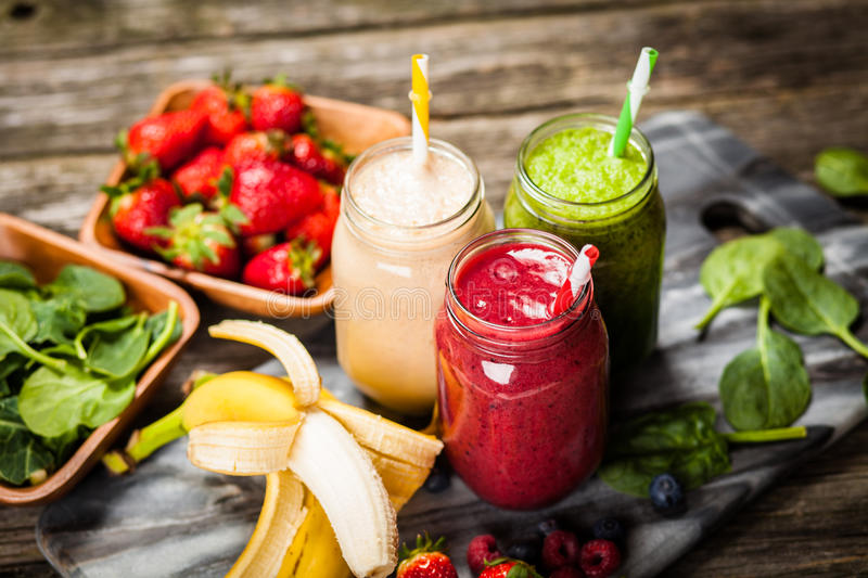 Milkshakes and smoothies. Assortment of milkshakes and smoothies on wooden table stock images
