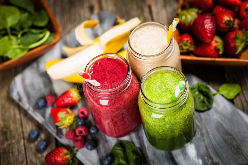 Milkshakes and smoothies. Assortment of milkshakes and smoothies on wooden table royalty free stock photography