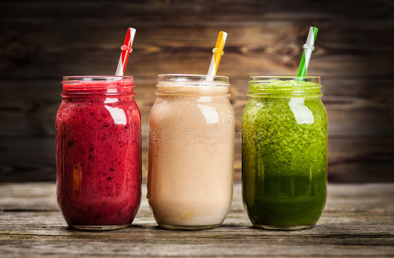 Milkshakes and smoothies. Three milkshakes and smoothies on wooden table royalty free stock photography