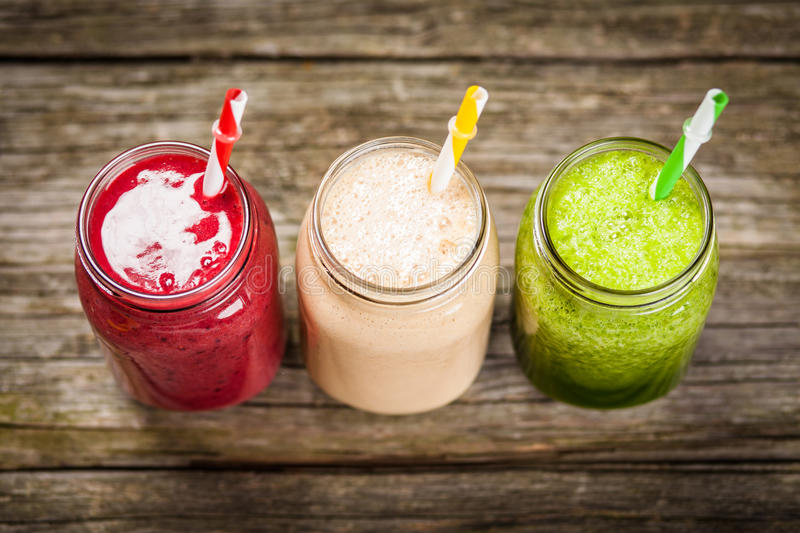 Milkshakes and smoothies. Three milkshakes and smoothies on wooden table stock images