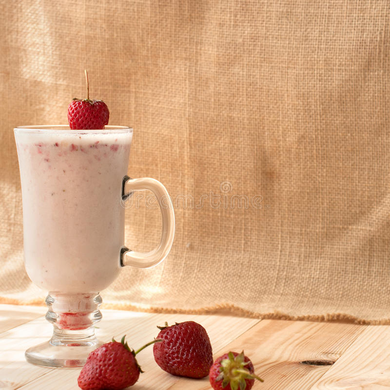 Milkshakes with strawberries. Strawberry milkshakes in tall glasses and bowl of strawberries stock photography