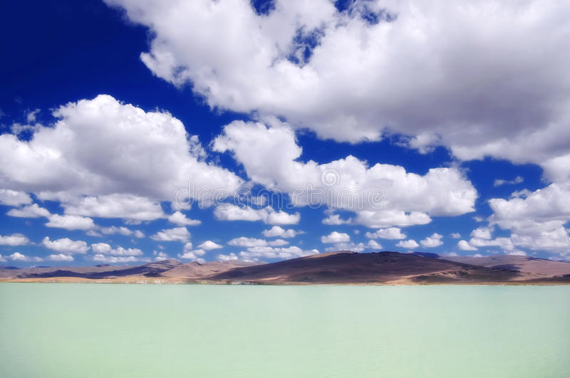 Milky bright turquoise glacier lake under the blue sky and white clouds. The Ukok Plateau, Altai Mountains, Siberia, Russia stock photography