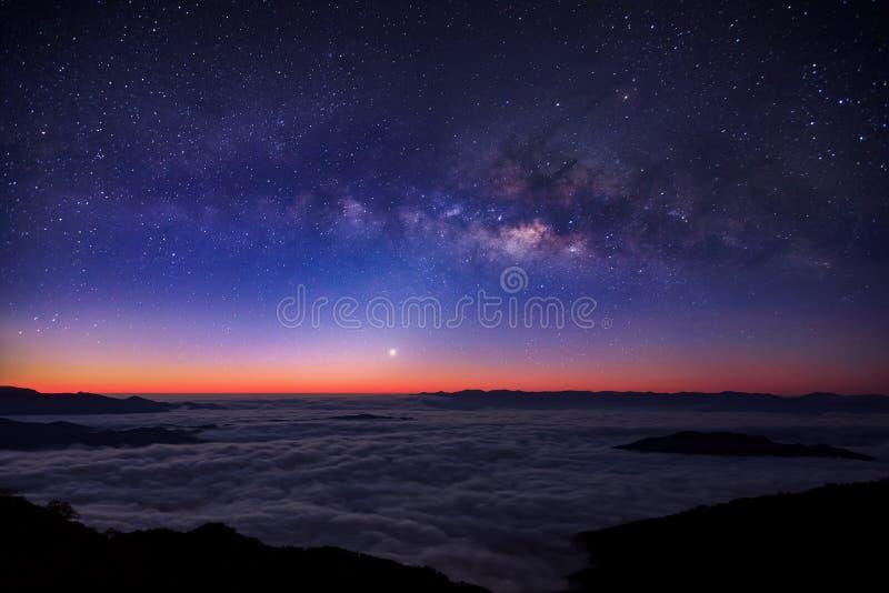 Milky sposób na nocnym niebie nad mgłową górą obrazy stock