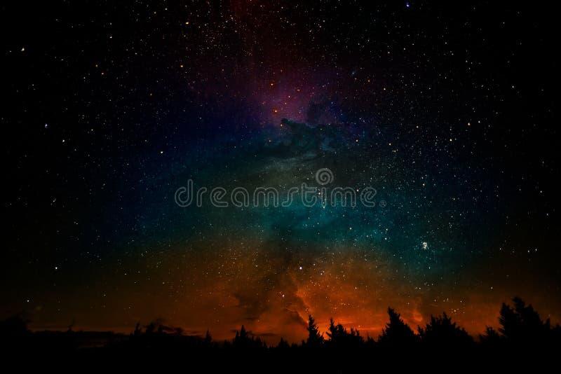Milky sposobu i fantazi galaxy chmurnieje nad lasowy krajobraz, kolaż fotografia royalty free