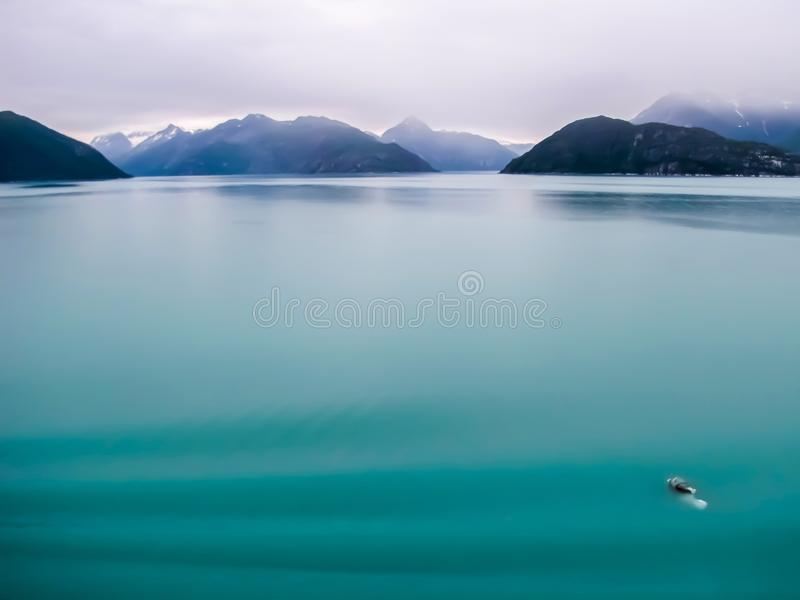 Milky Turquoise Green Glacier Ocean with Mountains on Horizon. Turquoise ocean water in Glacier Bay Alaska with one tiny iceberg in the foreground and mountains stock photos