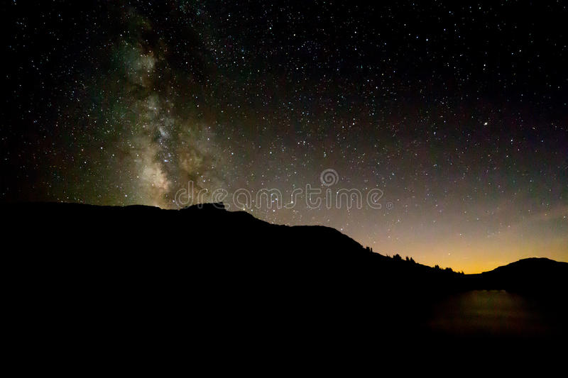 Milky Way above black silhouette of mountain with sunset glow re royalty free stock photo