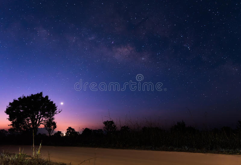 The milky way above dirt road before sunrise royalty free stock photography