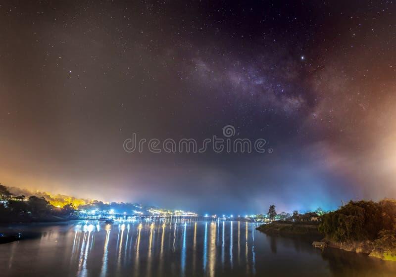The Milky Way is above the old wooden bridge Mon Bridge stock photo