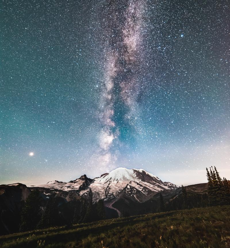 The Milky way galaxy over Mt Rainier. The Milky way protruding from the top of Mt Rainier. the foreground and mountain are lit by a rising moon stock photo