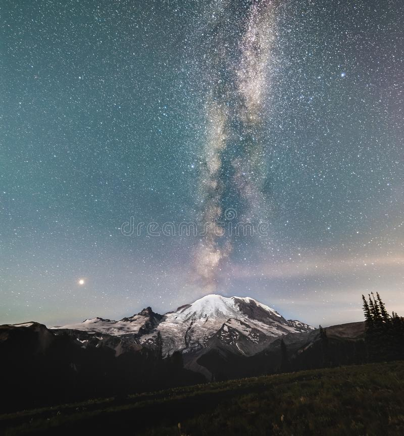 The Milky way galaxy over Mt Rainier. The Milky way protruding from the top of Mt Rainier which is lit by a rising moon royalty free stock image
