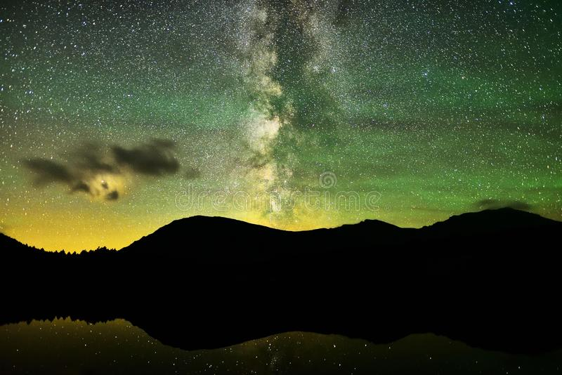 Milky Way over alpine lake. Milky way galaxy and red planet mars behind clouds. Bright stars are reflected in alpine lake Krugsee in front of mountain range in stock images