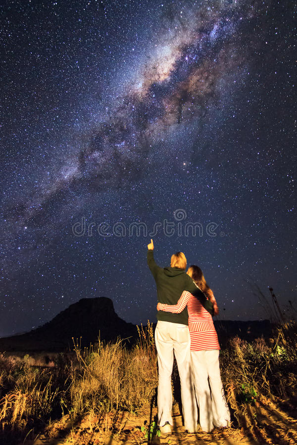 Milky way love. Lovely couple looking at the milky way on a romantic dark night in Isalo, on the island of Madagascar