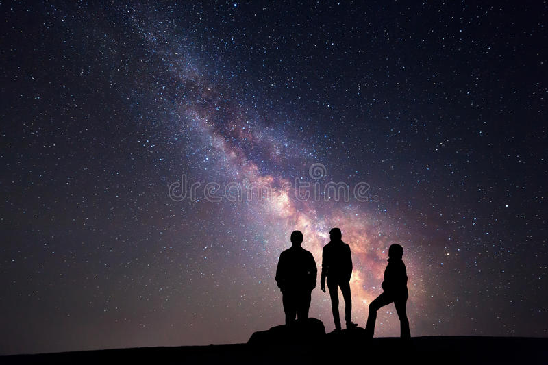 Milky Way. Night sky and silhouette of a family. Milky Way. Night sky with stars and silhouette of a happy family with raised-up arms royalty free stock photos