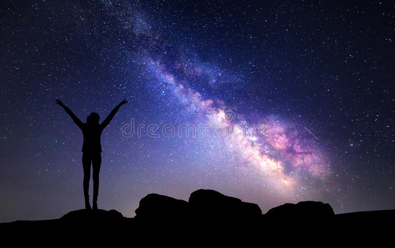 Milky Way. Night sky with stars and silhouette of a woman. With raised-up arms royalty free stock image