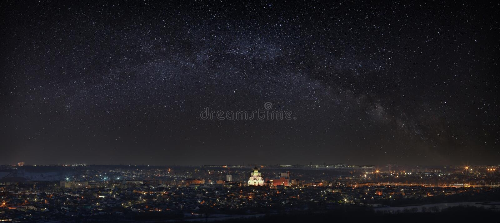 Milky Way over the city. Bright stars in the night sky. The streets are lit by lanterns. Panoramic view of the Orthodox Church. Milky Way over the city. Bright stock photo