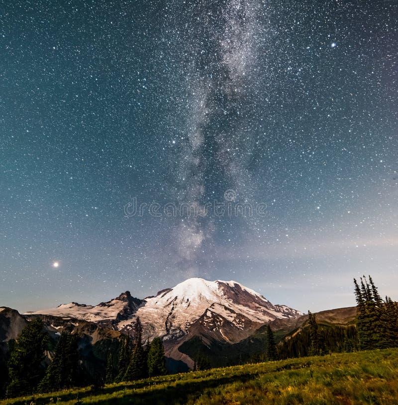 The Milky way galaxy over Mt Rainier. The Milky way over Mt Rainier. The rising moon has lit the forground stock image