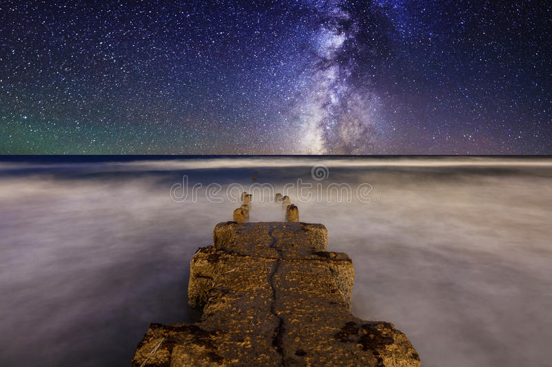 Milky Way over the pier at sea. During a storm royalty free stock photography