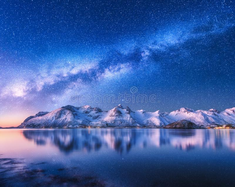 Milky Way over snow covered mountains and sea at night in winter royalty free stock photo