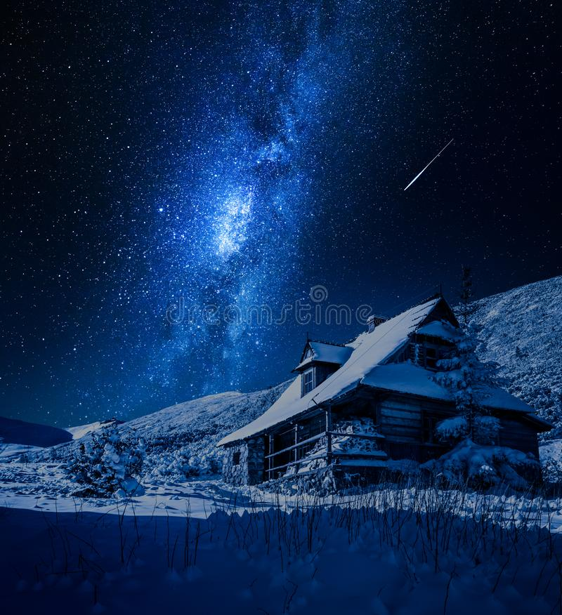 Milky way over wooden mountain cottage in winter, Poland royalty free stock photos