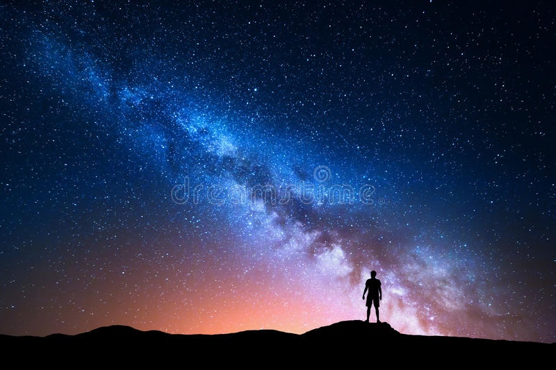 Milky Way and silhouette of alone man. Night landscape. Milky Way. Beautiful night sky with stars and silhouette of a standing alone man on the mountain. Blue royalty free stock photography