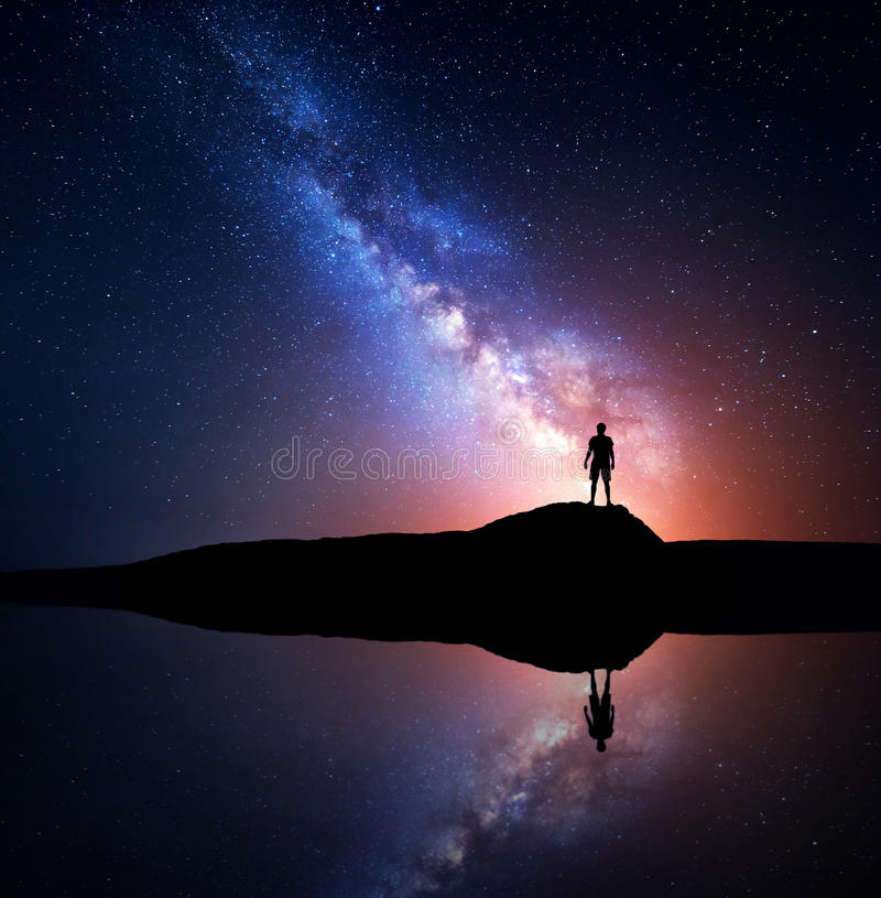 Milky Way and silhouette of a standing alone man. Milky Way. Night sky with stars and silhouette of a standing alone man on the mountain near the lake with stock photo