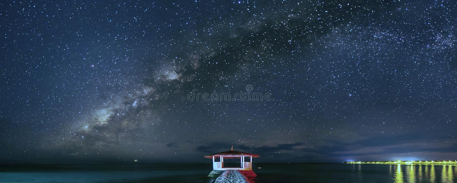 The milky way star in night scape. Night scape on maldives resort star and dark nigh over the sea show lighting stock photo