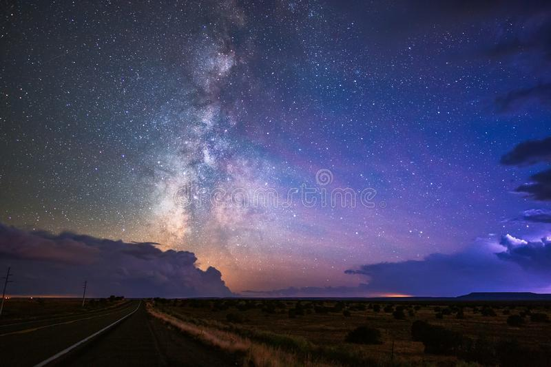 The Milky Way and starry night sky between thunderstorm clouds. royalty free stock photo