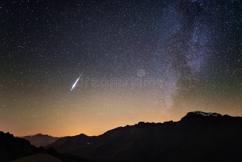 Milky Way and starry sky from high up on the Alps. Real Christmas comet in the sky. Majestic high mountain range with glacier and royalty free stock images
