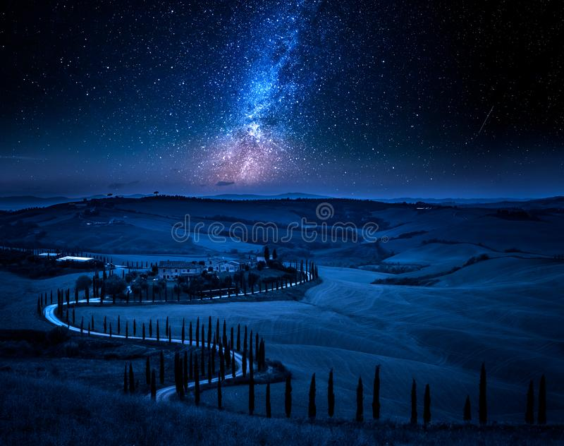 Milky way and winding road with cypresses, Tuscany stock photography