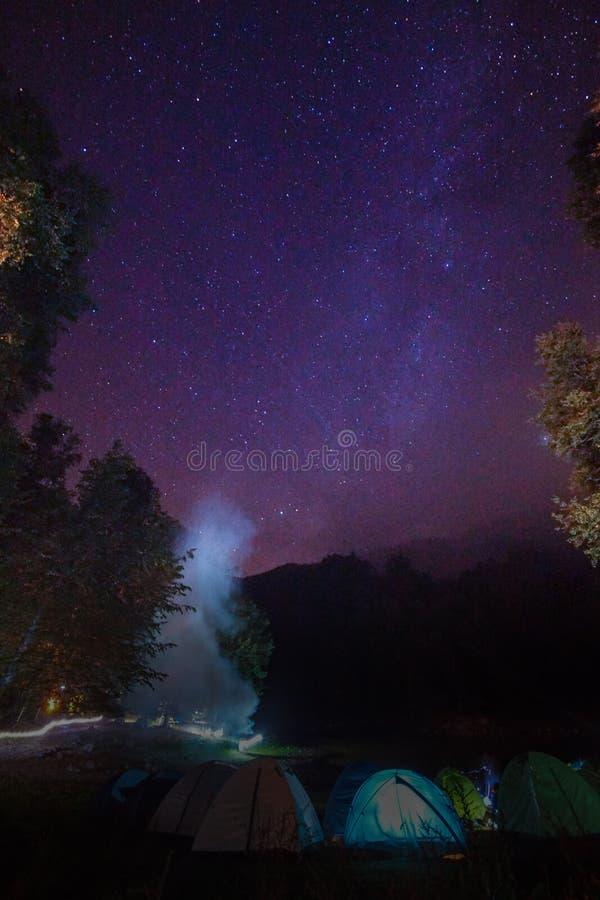 Milkyway e a fogueira fumam sobre uma área de acampamento fotografia de stock royalty free