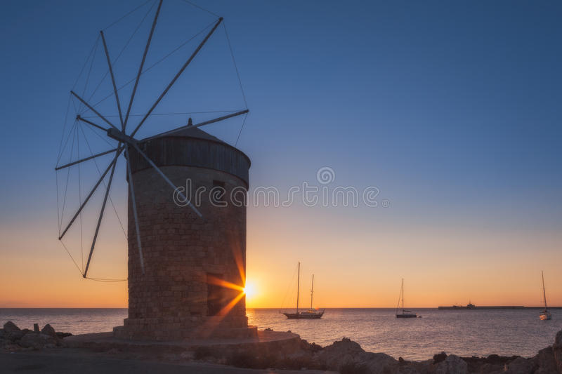 Mill on the background of the rising sun in the harbor of Mandraki. Rhodes Island. Greece. Attraction of the island of Rhodes is the capital of the ancient port royalty free stock image