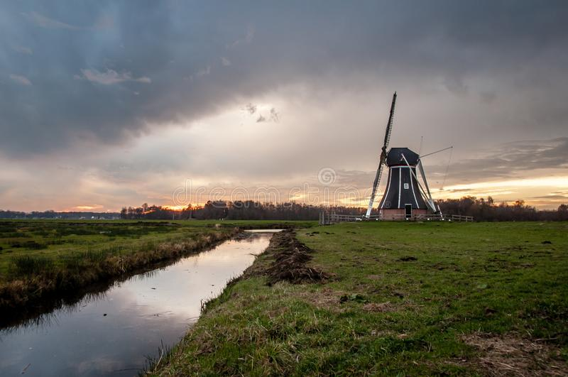 Mill in the dutch farmlands. Near Groningen. Nice sunset and lights royalty free stock photography
