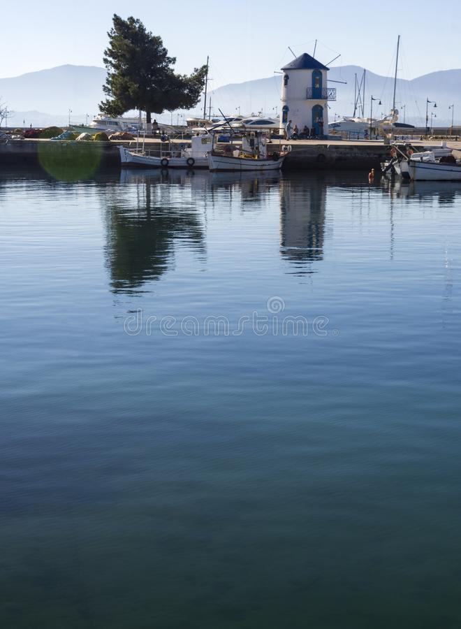 Mill and fishing boats in the calm Aegean Sea on a sunny day on the island of Evia, Greece stock images
