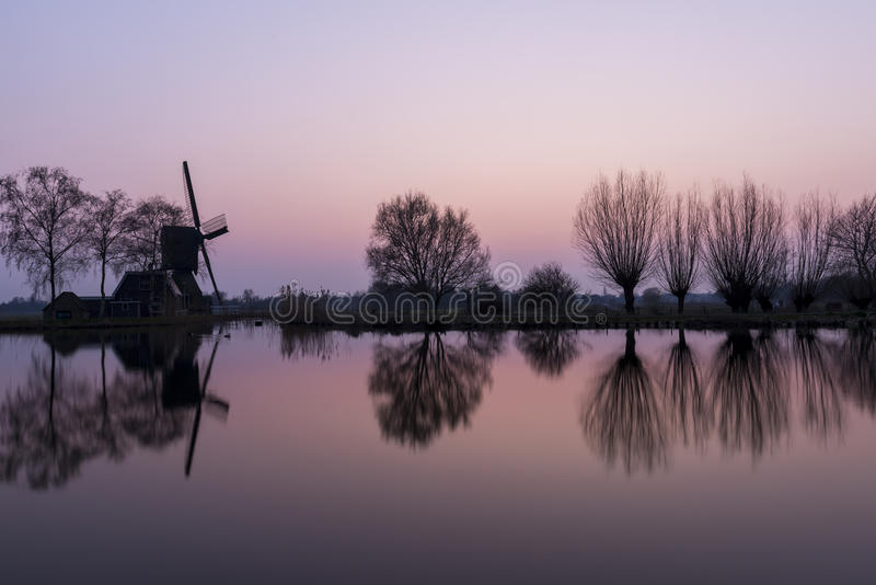 Mill and Trees at Woerdense Verlaat. Mill at Woerdens Verlaat after sunset near the Kromme Mijdrecht and with refelection in the water royalty free stock photography