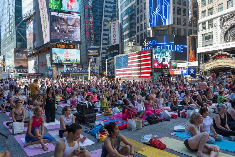 Millares de neoyorquinos que practican yoga en Times Square foto de archivo libre de regalías