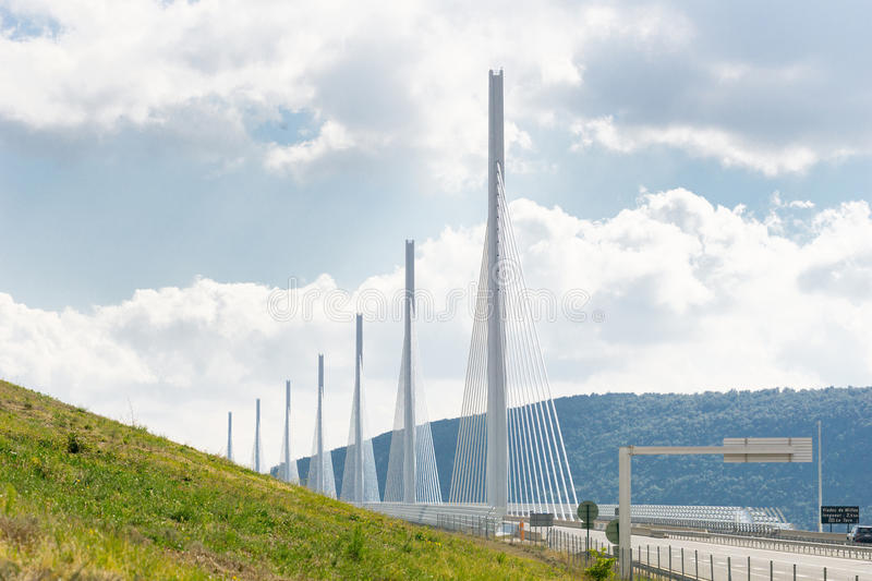 Millau Bridge piers disappear between distant hills across valley and green grassy slope, France. Stunning architecture of Millau Bridge piers disappear between royalty free stock photos