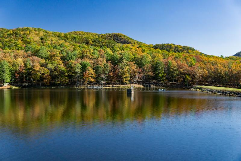 An Autumn View of Douthat Lake. Millboro, VA – October 26th: An Autumn view of Douthat Lake with fishing boat by the dam at Douthat Lake State Park royalty free stock images