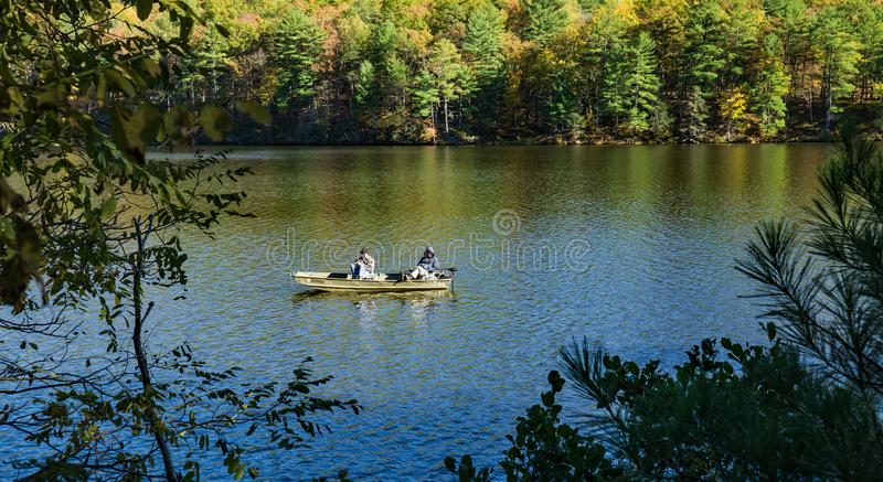 Couple Fishing for Trout on Douthat Lake. Millboro, VA – October 26th: Couple fishing for trout on a beautiful autumn day on Douthat Lake in Douthat Lake royalty free stock photos