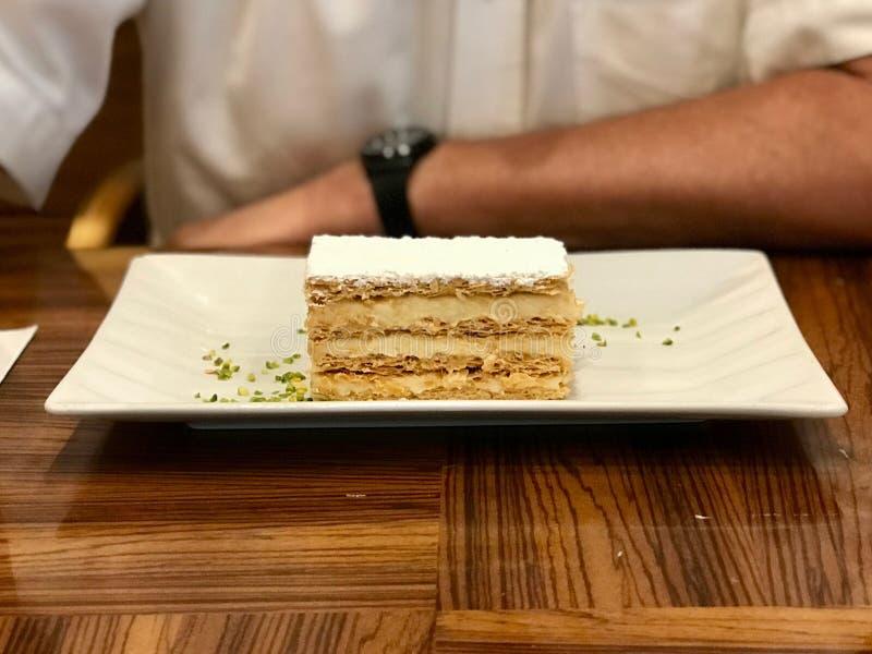 Mille Feuille Layer Cake con crema servita al ristorante immagini stock libere da diritti