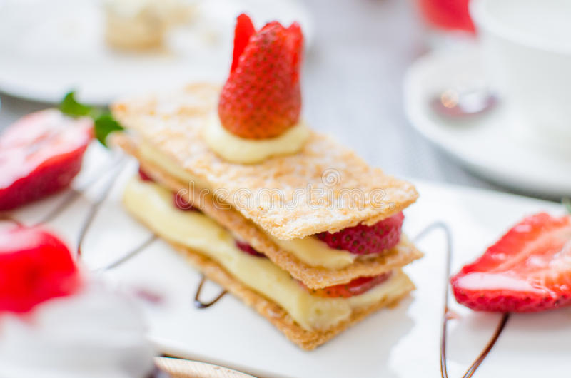 Mille feuille, puff pastry layered with strawberries and whipped. Cream in Tea set royalty free stock image