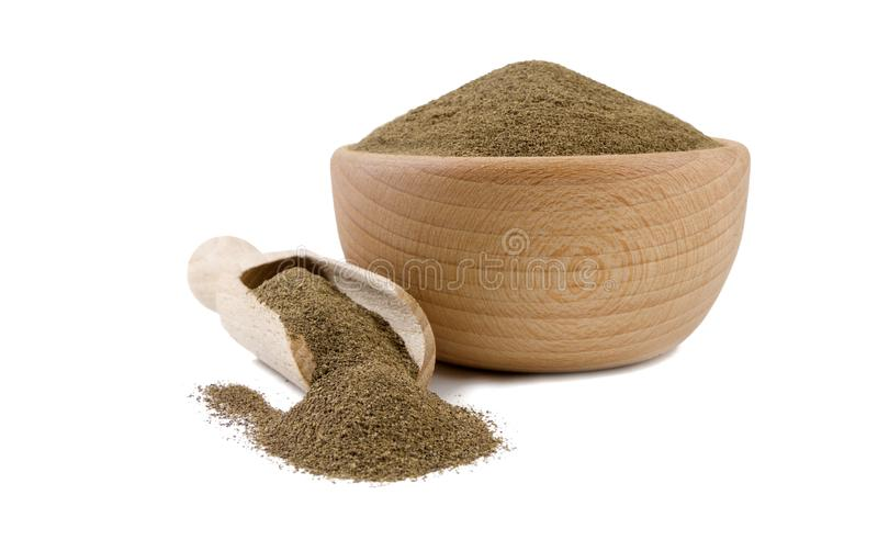 Milled or ground black pepper in wooden bowl and scoop isolated on white background. Spices and food ingredients.  royalty free stock photos