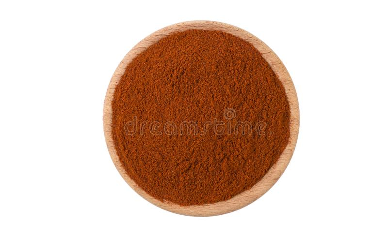 Milled or ground paprika or red pepper in wooden bowl isolated on white background. Spices and food ingredients stock photography