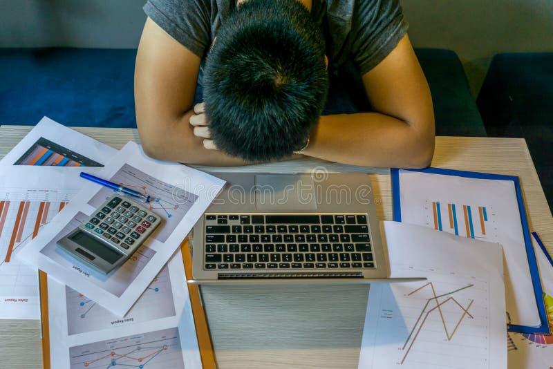 Millenari esauriti cadono addormentato sullo scrittorio con il computer portatile, documento unorganized immagine stock libera da diritti