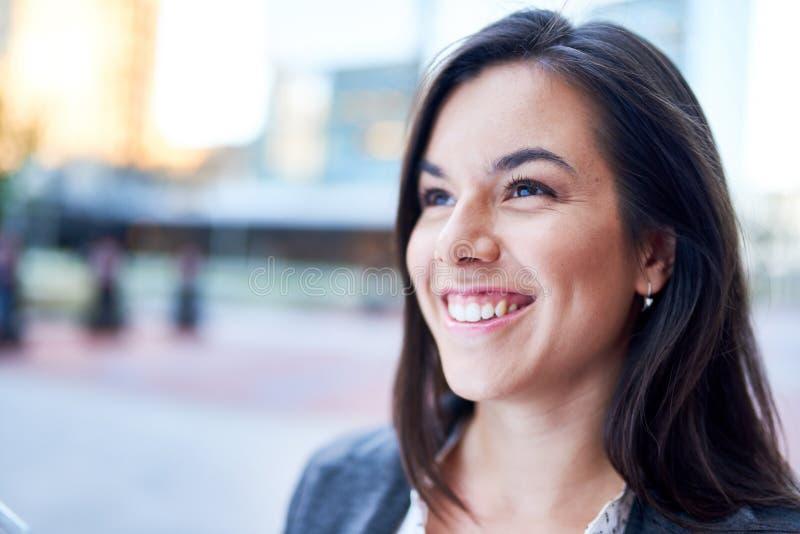 Millenial affärskvinna som säkert ler med cityscapebakgrund arkivbilder