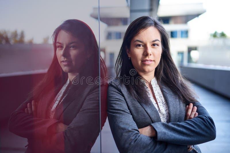 Millenial affärskvinna som säkert lutar på en mörk glasvägg med cityscapebakgrund arkivfoton