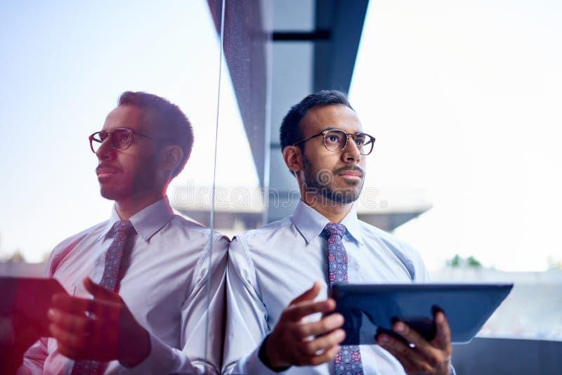 Millenial affärsman som säkert lutar på en mörk glasvägg med cityscapebakgrund royaltyfria foton