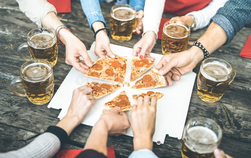 Millenial friends group drinking beer and sharing pizza slices at bar restaurant - Friendship concept with young people having fun stock photography